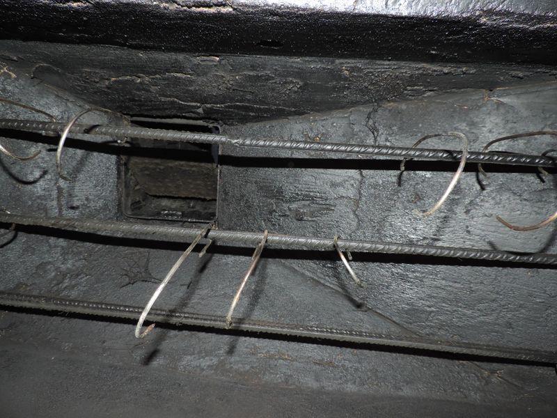 Góra komory wędzarniczej. Widać pręty do zawieszania haków oraz wylot dymu do komina