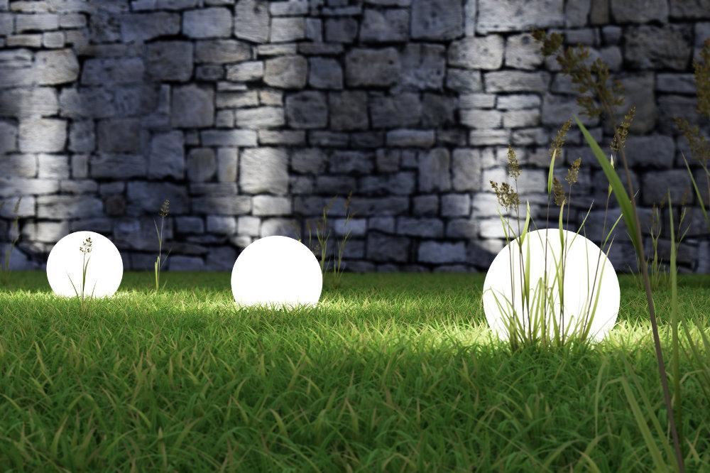 Świecące światła w trawie na tle starego muru